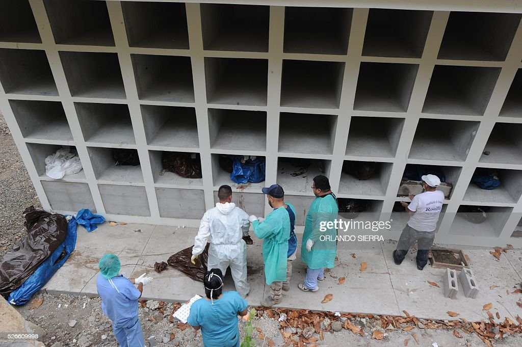 Forensic employees bury the bodies of 24 victims of violence in niches in a special cemetery for unidentified and unclaimed persons 14 km north of Tegucigalpa, on April 30, 2016. Honduras, no longer the most violent country in the world according to the government, reduced the murder rate since President Juan Orlando Hernandez took office in January 2014, from 75.1 homicides per 100,000 population in late 2013 to 56.7 in April 2016. / AFP / ORLANDO