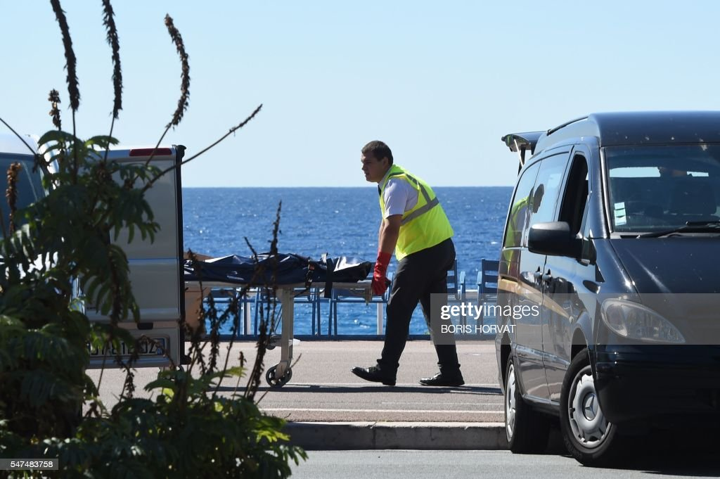 TOPSHOT - A forensic expert evacuates a dead body on the Promenade des Anglais seafront in the French Riviera city of Nice on July 15, 2016, after a gunman smashed a truck into a crowd of revellers celebrating Bastille Day, killing at least 84 people. Authorities said they found identity papers belonging to a 31-year-old French-Tunisian citizen in the 19-tonne truck, and that the driver had fired a gun several times before police shot him dead. / AFP / BORIS