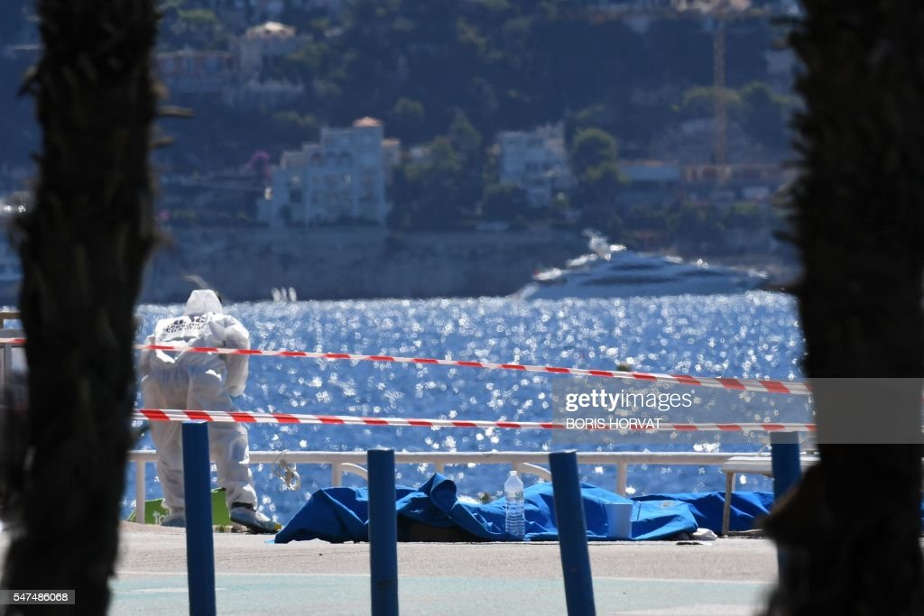 TOPSHOT - A forensic expert examines dead bodies covered with a blue sheet on the Promenade des Anglais seafront in the French Riviera city of Nice on July 15, 2016, a day after a gunman smashed a truck into a crowd of revellers celebrating Bastille Day, killing at least 84 people. Authorities said they found identity papers belonging to a 31-year-old French-Tunisian citizen in the 19-tonne truck, and that the driver had fired a gun several times before police shot him dead. / AFP / BORIS
