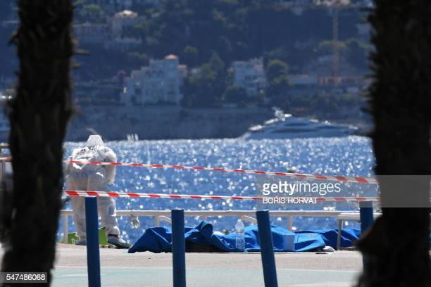 TOPSHOT A forensic expert examines dead bodies covered with a blue sheet on the Promenade des Anglais seafront in the French Riviera city of Nice on...