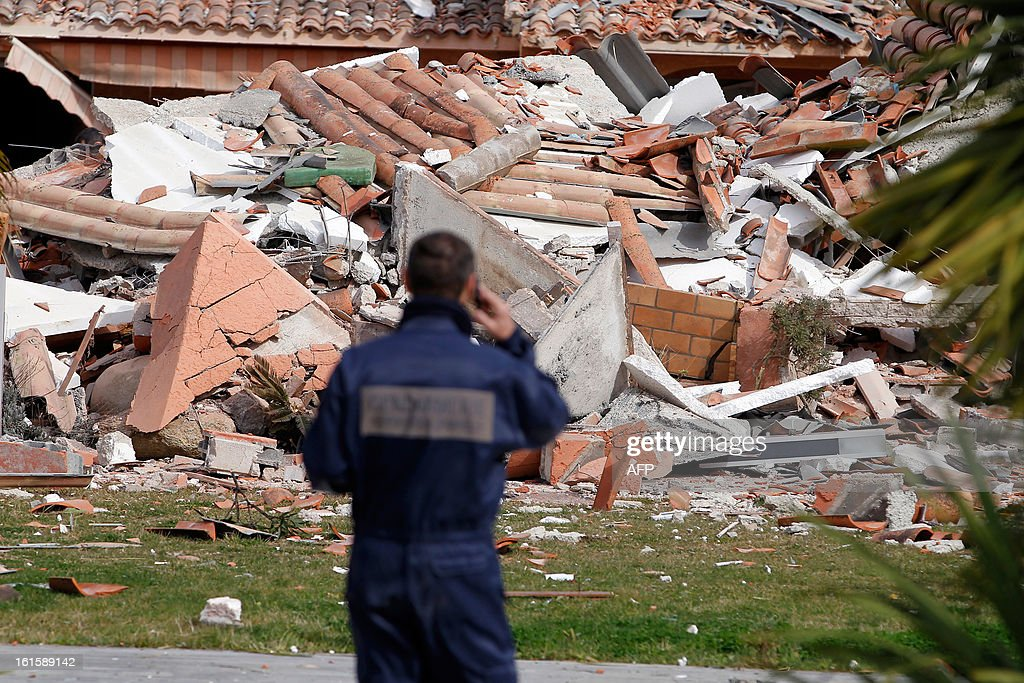 A forensic expert investigates around a house destroyed by a blast, injuring a man and a child, on February 12, 2013, in Porto-Vecchio, in the French Mediterranean island of Corsica. The reasons of the blast are still unknown. AFP PHOTO / PASCAL POCHARD-CASABIANCA