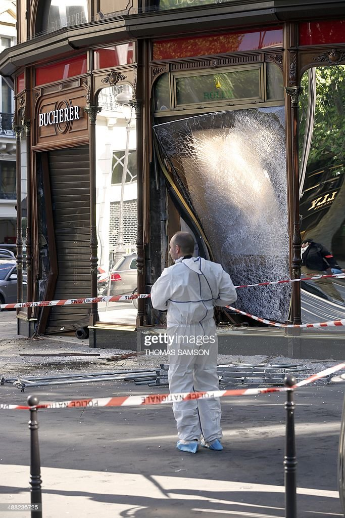 A forensic expert looks for evidence outside the jewellery store which was attacked by unidentified men with a motorized battering ram (L) on May 5, 2014 in Paris' Opera district.