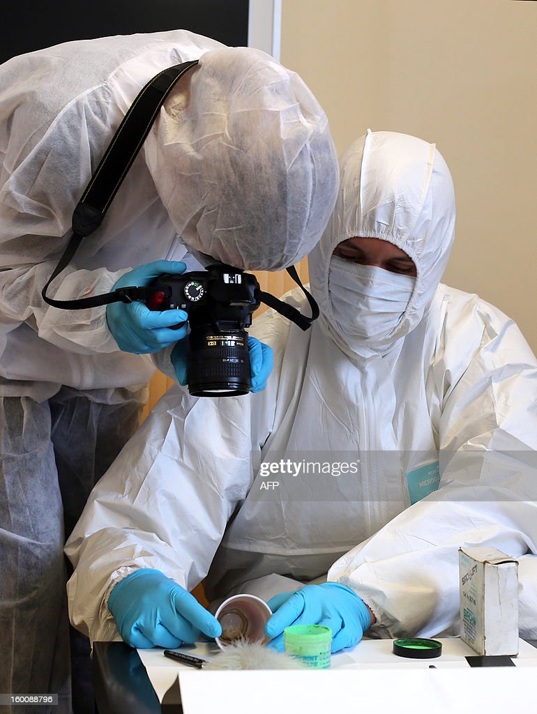 A forensic expert takes pictures while an other picks up clues during a mock exercise to present the work of a Police Technique et Scientifique (PTS, technical and scientific police) unit, on January 25, 2013 at Poissy, west of Paris.