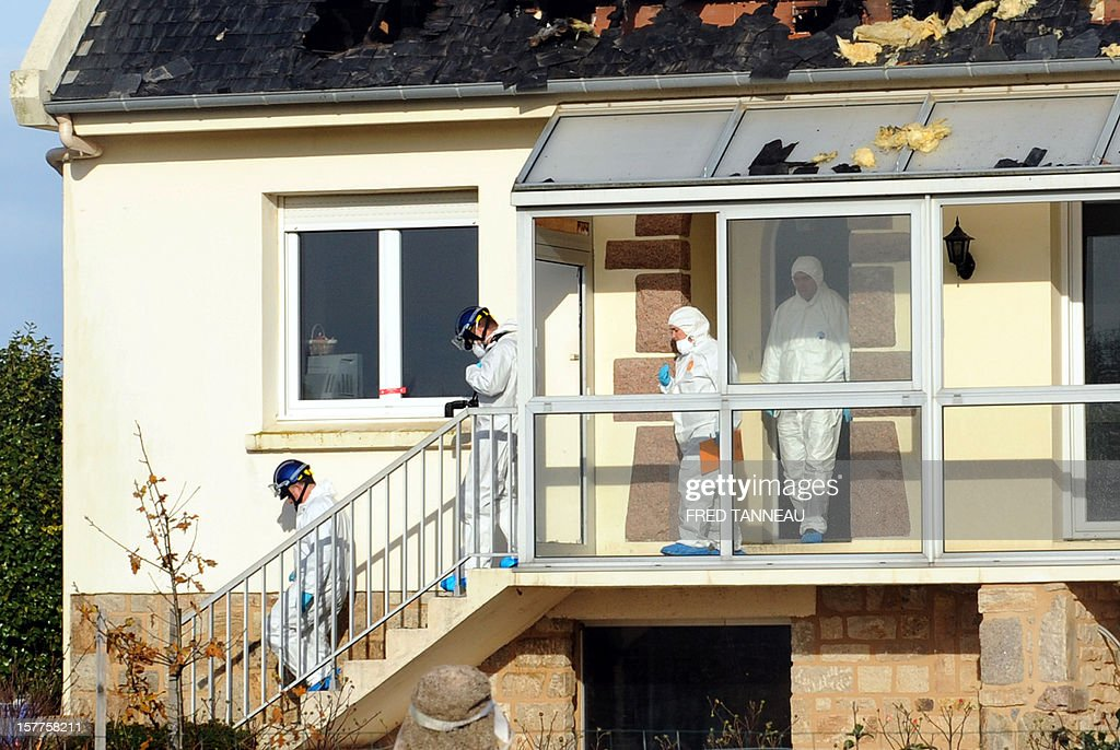 Forensic experts inspect a burnt house where the bodies of four people apparently belonging to the same family were found on December 6, 2012 in Plouescat, Brittany. AFP PHOTO / FRED TANNEAU
