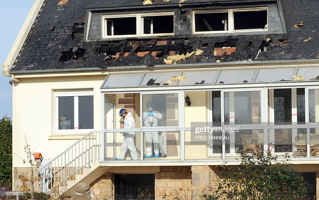Forensic experts inspect a burnt house where the bodies of four people apparently belonging to the same family were found on December 6, 2012 in Plouescat.