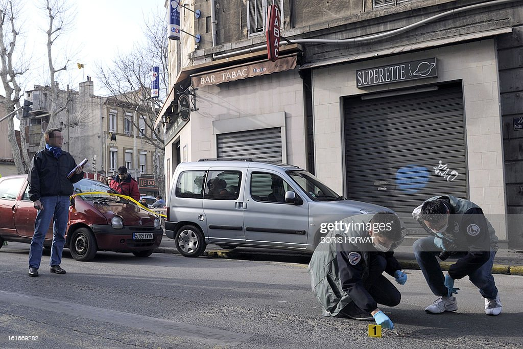 Forensic experts of the French police are at work at the site where a policeman allegedly shot dead a young man overnight, on February 14, 2013 in Marseille.