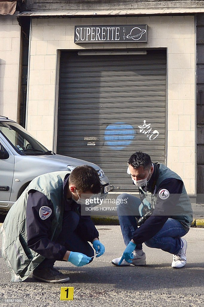 Forensic experts of the French police are at work at the site where a policeman allegedly shot dead a young man overnight, on February 14, 2013 in Marseille. AFP PHOTO / BORIS HORVAT