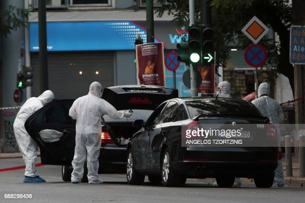 Forensic experts of the police search for evidence in and around the car of Greek former prime minister Lucas Papademos in Athens on May 25 after...