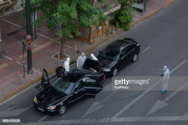 Forensic experts of the police search for evidence in and around the car of Greek former prime minister Lucas Papademos in Athens Greece 25 May 2017...