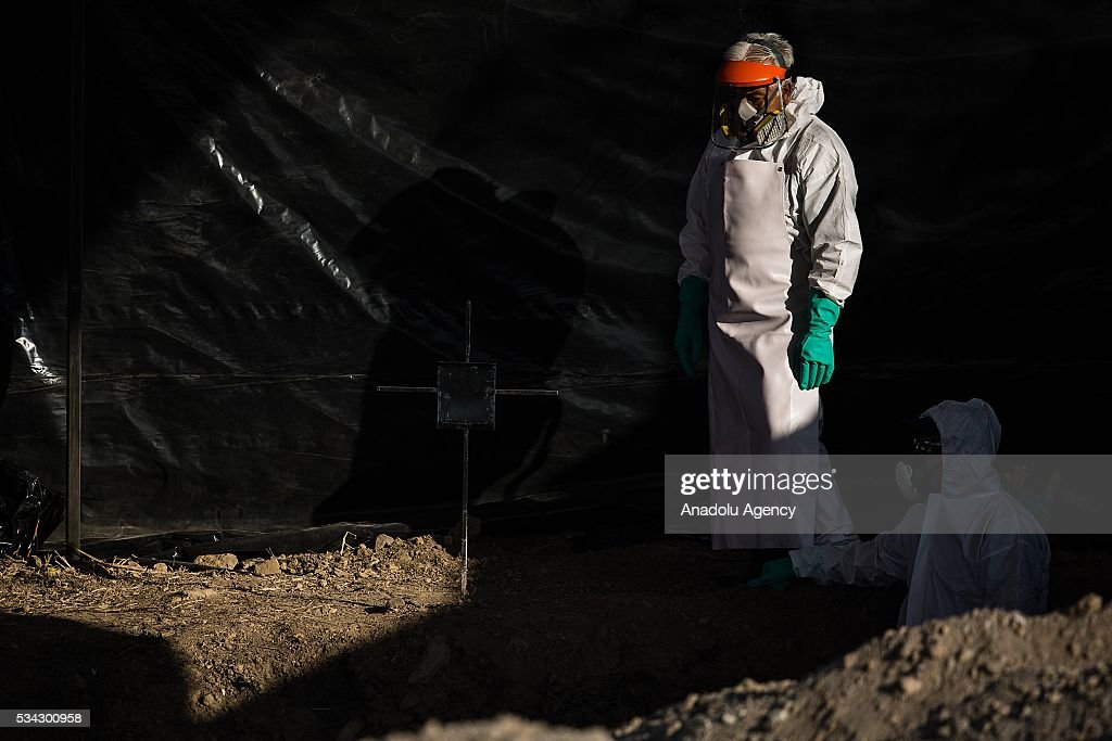 Forensic experts work in the graves where 116 bodies were found buried in Tetelcingo, Mexico on May 25, 2016.