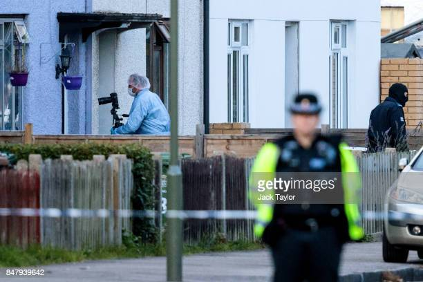 A forensic officer and an investigator wearing a balaclava at the scene on Cavendish Road during a raid in connection with the terror attack at...
