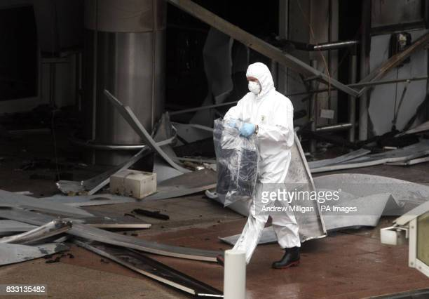 A forensic officer carries a gas canister wrapped in plastic from the scene of yesterday's dramatic attack on the terminal building at Glasgow Airport
