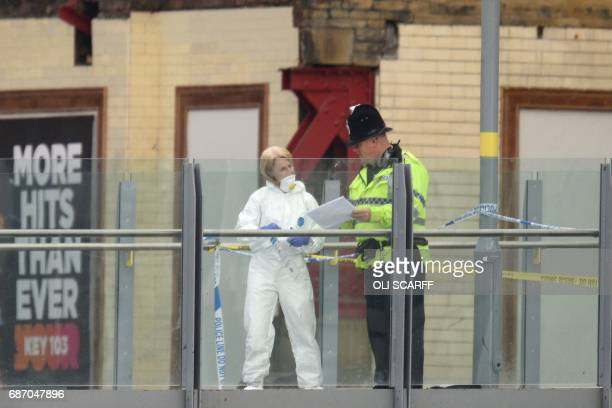TOPSHOT A forensic officer collects evidence on a walkway between Victoria station and Manchester Arena following a deadly terror attack in...