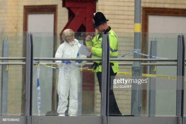 A forensic officer collects evidence on a walkway between Victoria station and Manchester Arena following a deadly terror attack in Manchester...