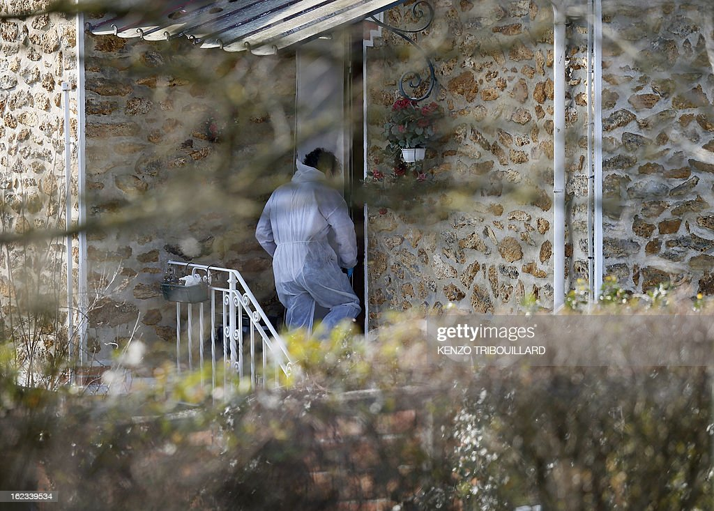 A forensic officer enters to look for evidence in the house where three children, aged 9, 11 and 17, two boys and their sister, were found dead by their father, on February 22, 2013, in Dampart, east of Paris. They were presumably throat-cutting according to police sources. The mother is missing and unreachable.