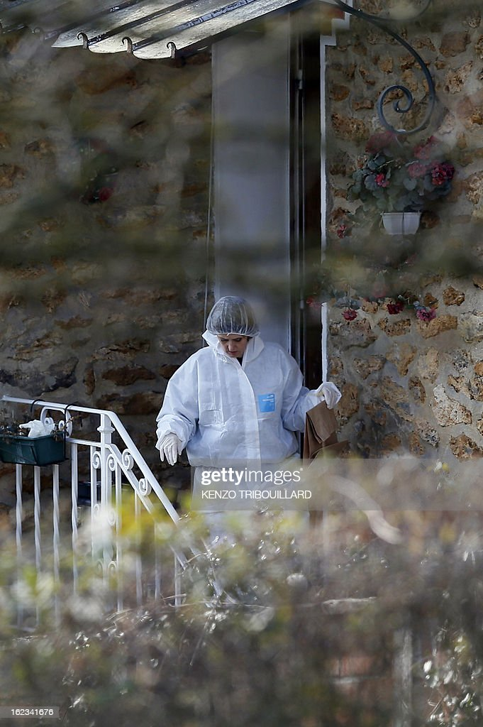 A forensic officer leaves with a bag after looking for evidence in the house where three children, aged 9, 11 and 17, two boys and their sister, were found dead by their father, on February 22, 2013, in Dampart, east of Paris. They were presumably throat-cutting according to police sources. The mother is missing and unreachable. AFP PHOTO KENZO TRIBOUILLARD
