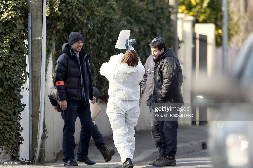 A forensic officer (C) looks at a paper as she speaks with policemen near the house where three children, aged 9, 11 and 17, two boys and their sister, were found dead by their father, on February 22, 2013, in Dampart, east of Paris. They were presumably throat-cutting according to police sources. The mother is missing and unreachable.