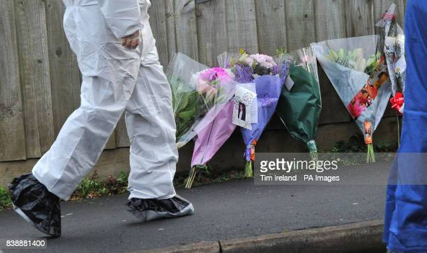A forensic officer outside the house on Mold Crescent in Banbury Oxfordshire where floral tributes have been left at the scene where Sally Cox and...