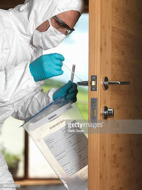 Forensic officer taking DNA swab off door handle