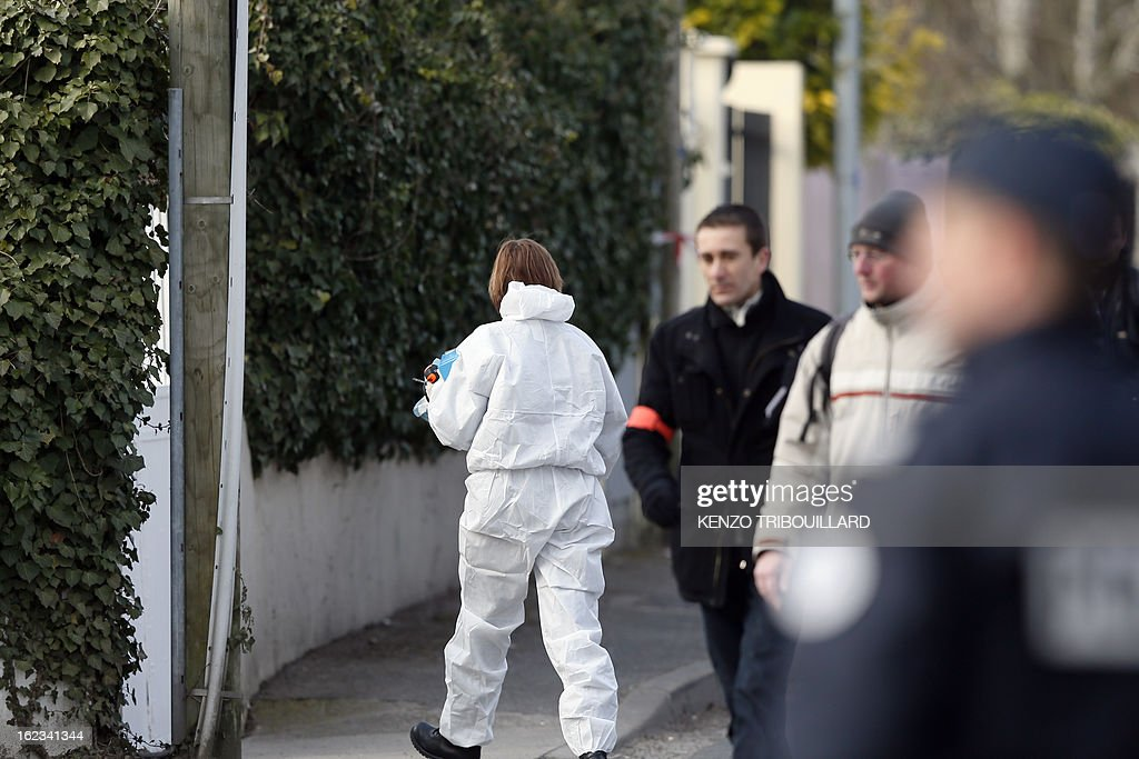 A forensic officer (C) walks near the house where three children, aged 9, 11 and 17, two boys and their sister, were found dead by their father, on February 22, 2013, in Dampart, east of Paris. They were presumably throat-cutting according to police sources. The mother is missing and unreachable. AFP PHOTO KENZO TRIBOUILLARD