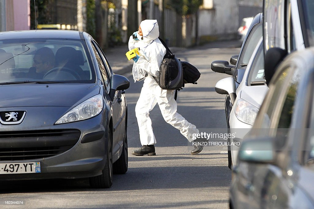 A forensic officer (L) walks near the house where three children, aged 9, 11 and 17, two boys and their sister, were found dead by their father, on February 22, 2013, in Dampart, east of Paris. They were presumably throat-cutting according to police sources. The mother is missing and unreachable.
