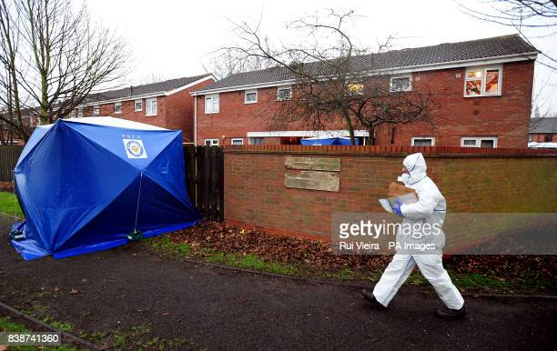 Forensic officers attend the scene after a woman died and a man is critical in hospital after being found with stab wounds at a house in Newhampton...