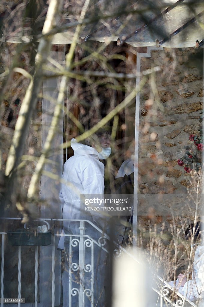 Forensic officers enter to look for evidence in the house where three children, aged 9, 11 and 17, two boys and their sister, were found dead by their father, on February 22, 2013, in Dampart, east of Paris. They were presumably throat-cutting according to police sources. The mother is missing and unreachable.