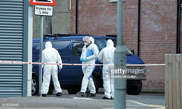 PSNI forensic officers inspect the damaged van following a suspected car bomb attack on a prison officer at Hillsborough Drive on March 4 2016 in...
