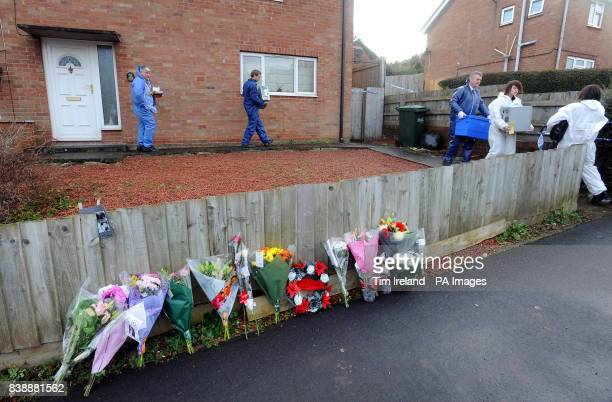 Forensic officers leave the house on Mold Crescent in Banbury Oxfordshire where floral tributes have been left at the scene where Sally Cox and...