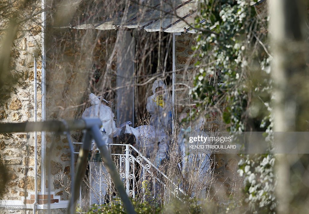 Forensic officers look for evidence at the entrance of the house where three children, aged 9, 11 and 17, two boys and their sister, were found dead by their father, on February 22, 2013, in Dampart, east of Paris. They were presumably throat-cutting according to police sources. The mother is missing and unreachable.