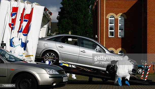 Forensic officers stand beside a Vauxhall vectra car at the Forth Street Mosque on July 3 2007 in Glasgow Scotland Bomb disposal carried out a series...