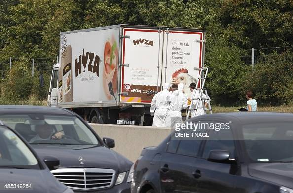 Forensic officers stand in front of a truck inside which were found a large number of dead migrants on a motorway near Neusiedl am See Austria on...