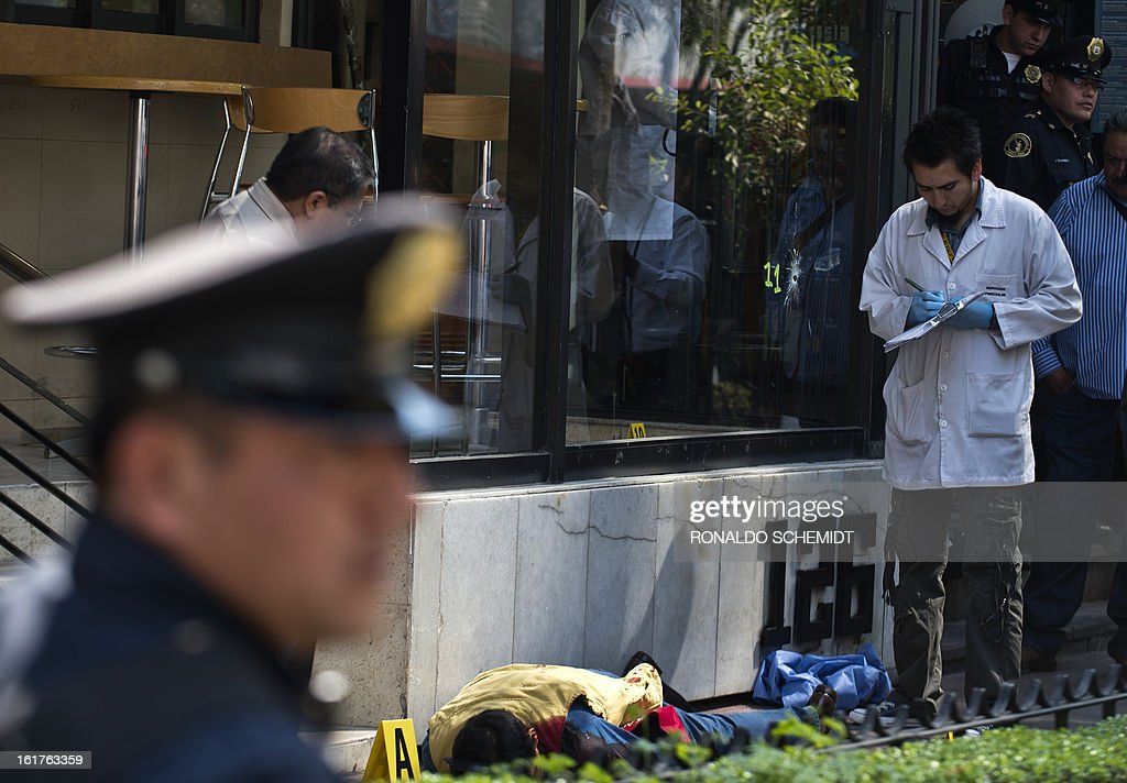 Forensic personnel and policemen work at the crime scene where a man was killed by a gunman, in the 'Zona Rosa', a commercial and tourist area of Mexico City, on February 15, 2013. AFP PHOTO/Ronaldo Schemidt