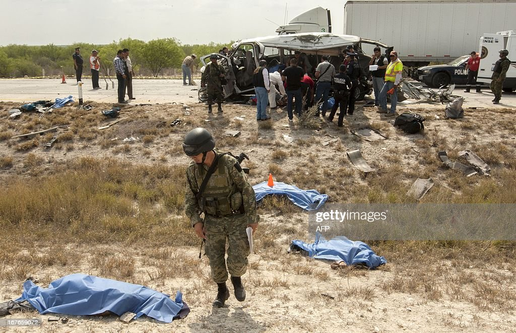 Forensic personnel and soldiers work at the site where ten members of the music band 'La Reyna de Monterrey' were killed in a road accident on the Monterrey-Laredo highway, in the municipality of Sabinas Hidalgo, Nuevo Leon state, Mexico on April 27, 2013. AFP PHOTO / Julio Cesar AGUILAR