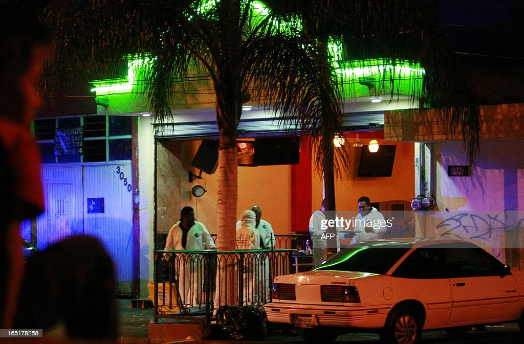 Forensic personnel arrive at the scene of a crime where four people were shot dead, in a bar of Guadalajara, Mexico, on March 31, 2013. Most crimes go unsolved in Mexico, but security experts say bar shootings may be linked to turf wars between drug gangs or a way for criminal groups to scare owners into paying extortion money. AFP PHOTO/STR
