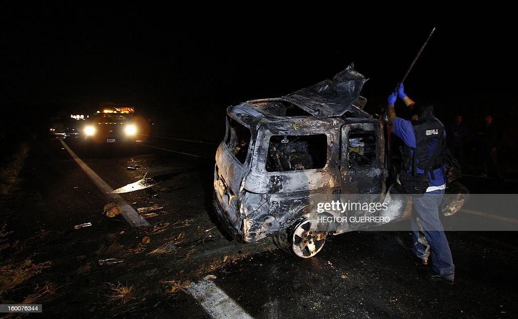 Forensic personnel inspect a destroyed vehicle in Magdalena, Jalisco State, Mexico on 25 January 2013. Five innocent civilians lost their lives during a clash between gangs of organized crime. AFP PHOTO/Hector Guerrero