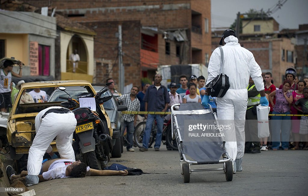 Forensic personnel inspect the corpse of a man killed by a member of a criminal gang, at the Commune 4 -- one of the shantytowns with the highest rates of urban violence and displacement in Medellin, Antioquia department, Colombia, on February 11, 2013. So far this year, 105 have been killed by urban conflict due to disputes between gangs for the control of the territory. Violent street gangs have 'invisible borders' that delineate their territories in Medellin, ranked the 14th most dangerous city in the world with a murder rate of 70 per thousand inhabitants in 2011. AFP PHOTO/Raul ARBOLEDA