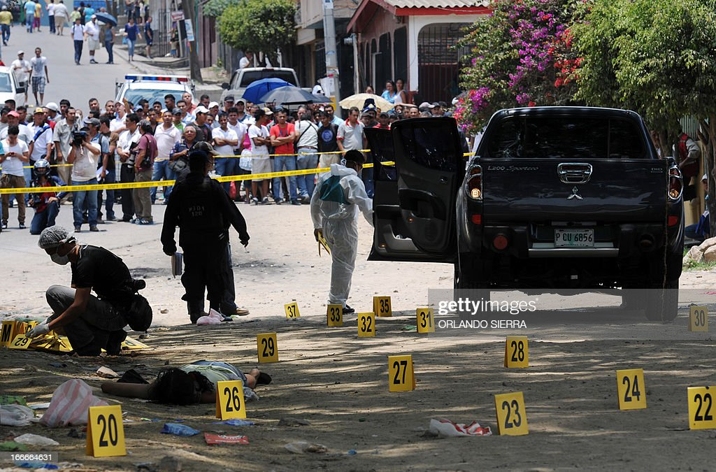 Forensic personnel inspect the crime scene in which five people -- including a high school student -- were shot dead in the suburb of La Haya, in northern Tegucigalpa, on April 15, 2013. In March 2012, the UN announced Honduras had the world's highest murder rate, at 82.1 deaths per 100,000 people, while a local observatory on violence put the rate at 86.5 per 100,000. AFP PHOTO/Orlando SIERRA