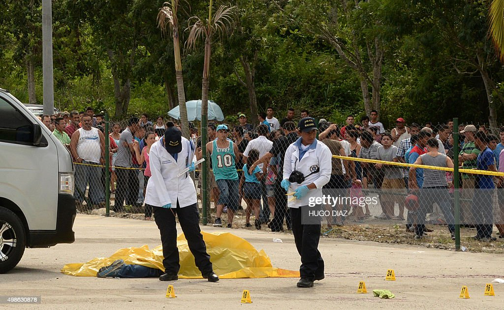 Forensic personnel inspect the scene where eight people were killed at a bus station in Choloma north of Tegucigalpa on November 24 2015 Eight people...