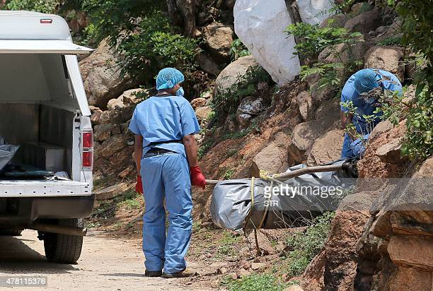 Forensic personnel load onto a van the body of one of the ten bodies found in clandestine graves in the tourist city of Acapulco Guerrero State on...