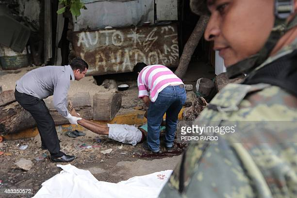 Forensic personnel move the body of a young man murdered on August 7 2015 in a street of Acapulco Mexico Guerrero is one of Mexico's poorest and most...