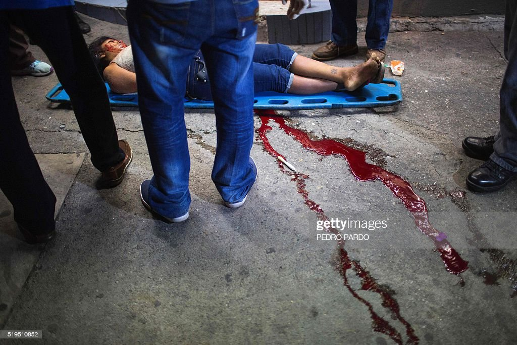 Forensic personnel stand before the body of a murdered woman in Acapulco Guerrero state Mexico on April 6 2016Guerrero is one of Mexico's poorest and...