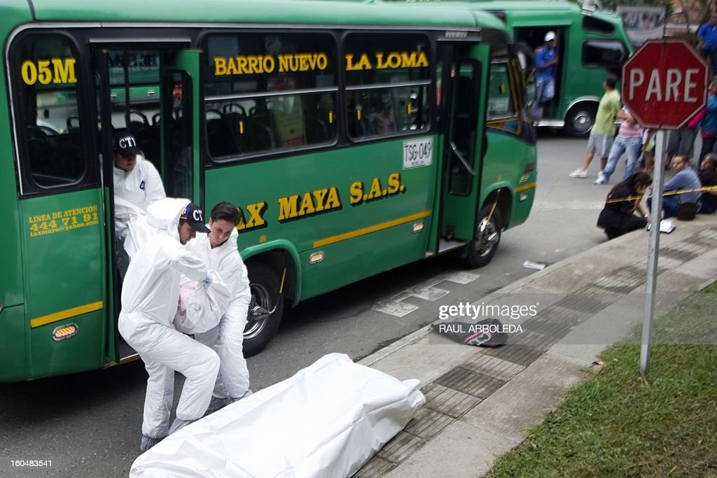 Forensic personnel unload from a bus the body of a Adriana Arroyave, chief dispatcher of a bus company linked to the subway, murdered by a member of a criminal gang, at Comuna 8, one of the shantytowns with the highest rates of urban violence and displacement due to disputes between gangs for the control of territory, in Medellin, Antioquia department, Colombia on February 1, 2013. AFP PHOTO/Raul ARBOLEDA