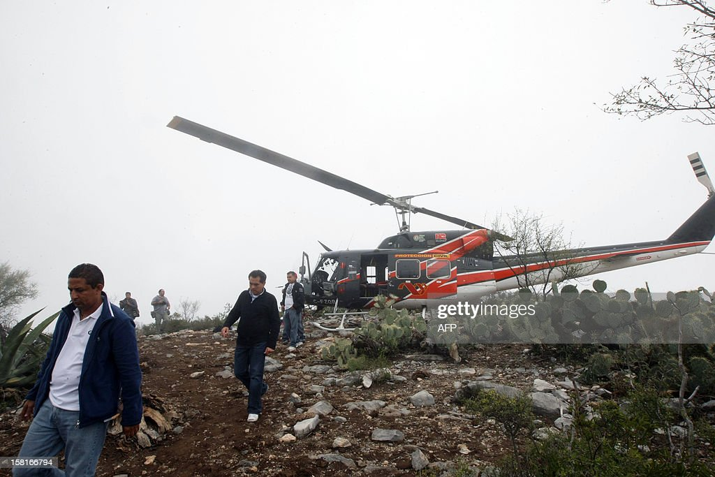 Forensic perssonnel look for the evidence in the area where a plane of Mexican-US singer Jenni Rivera crashed, on December 10, 2012, close to Iturbide, Mexico. The wreckage of a plane carrying Rivera has been found in northern Mexico and there were no survivors, officials said. The Lear Jet was flying from Monterrey to Toluca, and was carrying six other people besides the singer, said Iturbide's Mayor Antonio Gonzalez. AFP PHOTO / Julio Cesar Aguilar