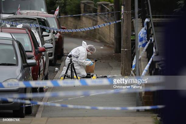 Forensic police examine and place a shoe into an evidence bag at the scene after Jo Cox Labour MP for Batley and Spen was shot and stabbed by an...