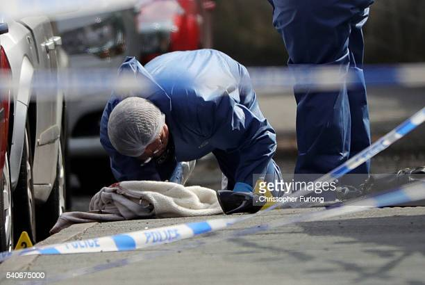 Forensic police examine clothing shoes and a handbag at the scene after Jo Cox Labour MP for Batley and Spen was shot and stabbed by an attacker at...
