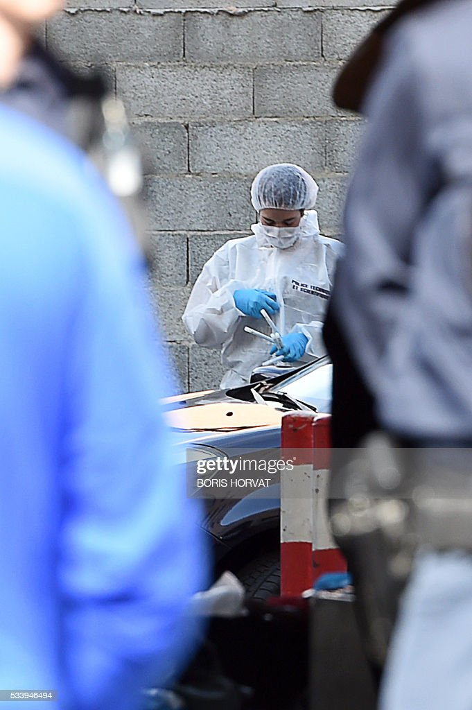 Forensic police investigate a crime scene next to the body of a man who was killed by gunshots in Marseille, southern France, on May 24, 2016. / AFP / BORIS