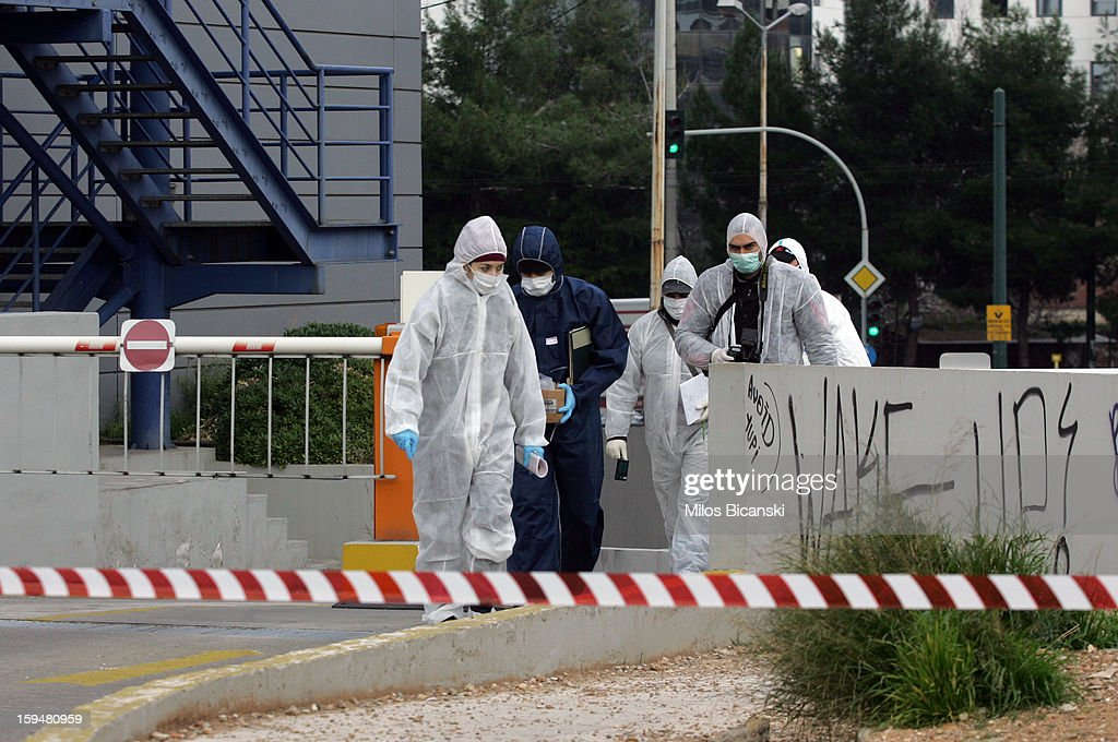 Forensic police investigate the scene after an unknown attacker fired an automatic rifle at the offices of the Ruling Party on January 14, 2013 in Athens, Greece. Nobody was injured in the attack which targeted the headquarters of the governing New Democracy party.
