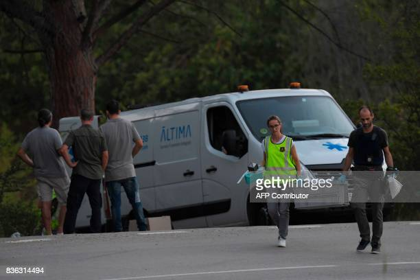 Forensic police members carry a box with evidences past the van of the funeral services carrying the body of Moroccan suspect Younes Abouyaaqoub on...