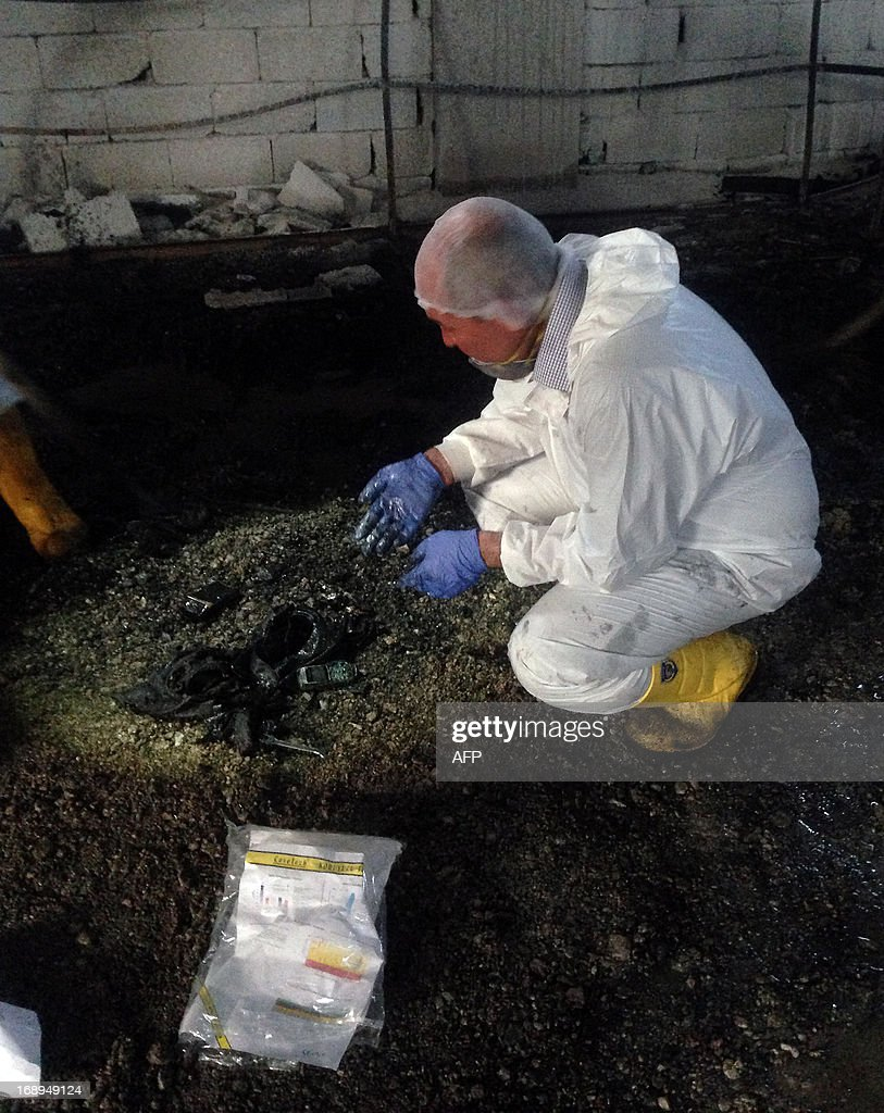 A forensic police officer works inside an illegal fuel depot on May 17, 2013, after suspects set ablaze the depot located in the basement of a three-storey building in a small village near Turkey's border with Syria, triggering a strong explosion that killed at least ten people and wounded nine others. Among the wounded were three suspected smugglers as well as several security officers, Anatolia news agency reported.